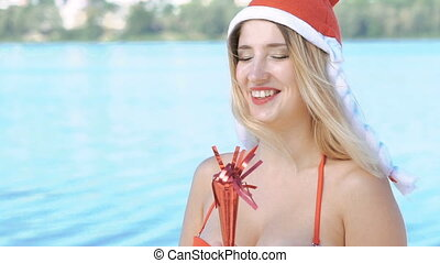 Girl with santa hat and swimsuit looking aside on sea...