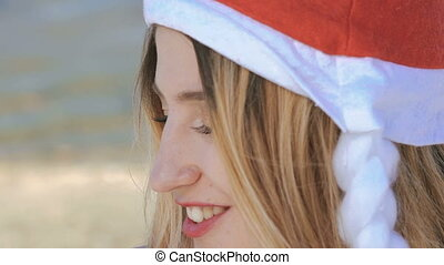 Close up girl in santa hat smiling and looking on camera....