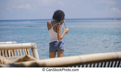 A girl with short hair, a T-shirt and denim shorts stands near the seaside on the island of Bali. She drinks a cocktail. Wonderful weather, the wind and the island promotes tranquility