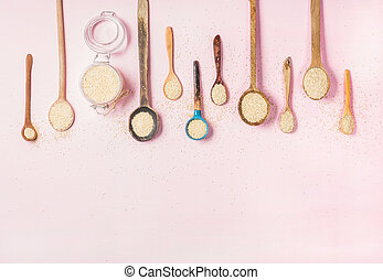 Quinoa seeds in different spoons and jar over pink...