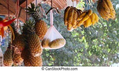 Street shop with fruit hanging for sale pineapple, banana,...