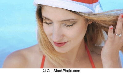 Pretty woman in santa hat flirting with camera on sea background. Slowly