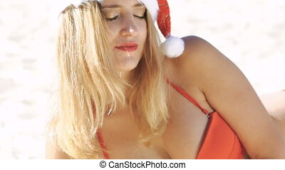 Girl in red swimsuit and santa hat flirting on the beach. Slowly