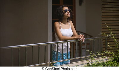 Funny girl in glasses on the porch outside his hotel room....
