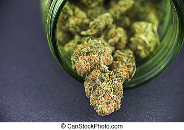 Detail of cannabis bud (crimson strain) on green glass jar -...