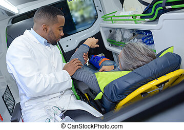 Paramedic holding arm of man in ambulance
