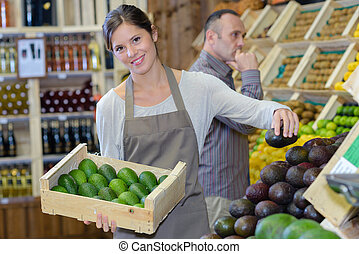 Woman stacking avocados in greengrocers