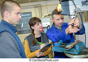 apprentices working on the machine - metal processing