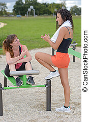Ladies chatting by park exercise equipment