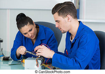 team of students examining and repairing computer parts