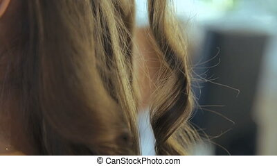 Professional hairdresser doing hairstyle for beautiful girl in salon