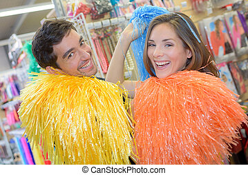 Man and woman with colorful pompoms