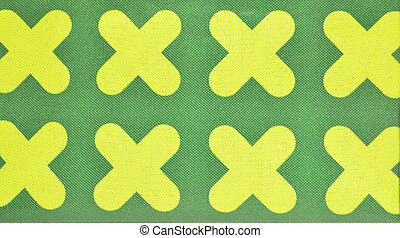 Yellow criss-cross symbol on green canvas fabric fiber for...