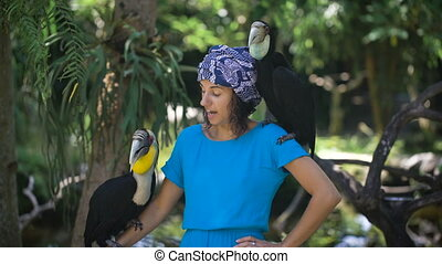 Tanned girl in a blue dress and a scarf on her head is in the rainforest, and tries to speak with parrots, fearing them which keeps on his arm and shoulder