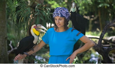 The girl in the park of birds and reptiles on the island of Bali. She in excellent mood is photographed with birds. Ptitsy-nosorgi at her on shoulders.
