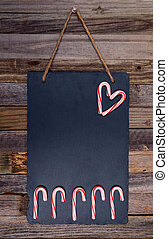Holiday candy cane heart shape and fence on dark stone board...