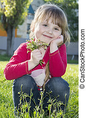 Spring in the park beautiful little girl sitting on the grass with a bouquet of flowers.