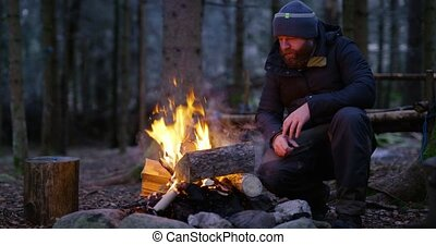 Man warms himself at camp fire in the woods - One pensive...