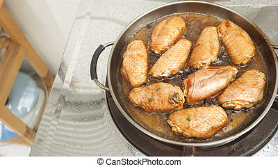 Marinated chicken wings cooking fried pan
