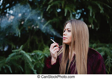 Pretty girl smoking in the park - Pretty blond girl with...