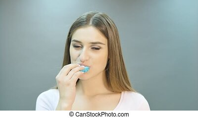 Young happy cute woman eating french macaroon