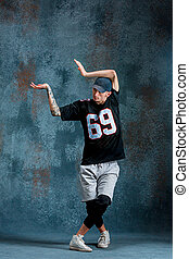 Young man break dancing on wall background. - Young man...
