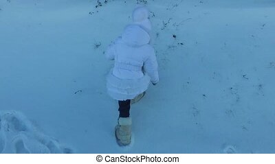 Girl child climbs the hill. The girl's face red from the cold weather. Frosty winter day