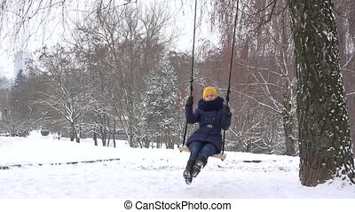 Woman on rope and wood swing under birch tree during winter time. 4K