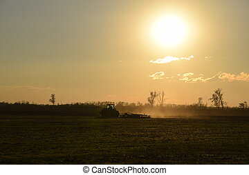 Tractor at sunset plow plow a field. Tilling the soil in the...