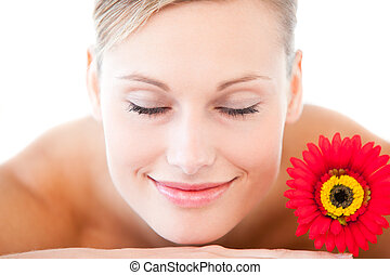 Close-up of a smiling woman lying on a massage table with a flower in a health spa