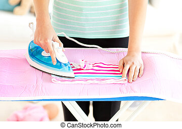 Close-up of a caucasian woman ironing her clothes against a...