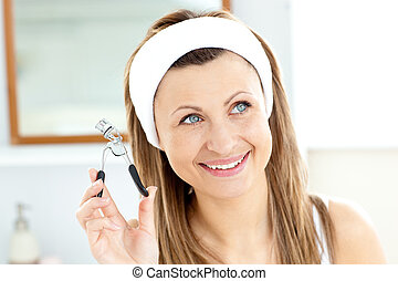 Smiling woman holding an eyelash curler looking at the camera in the bathroom at home