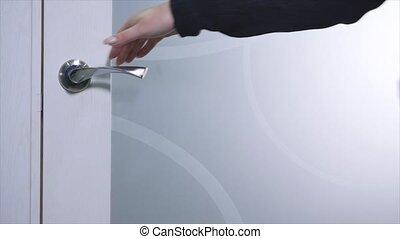 Hand opening the white door