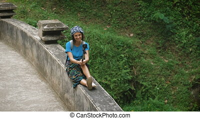 Smiling female traveler sittting on the railings of bridge on terrace and holding selfie-stick in her hands. Attractive brunette is trying to make selfie photo against a background of tropical plants.