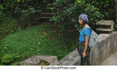 Lone woman with black hair, veiled headscarf, dressed in a blue T-shirt and kerchief tied around the legs, standing on the stone bridge in the middle of the green jungle and looking thoughtfully