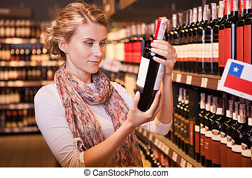 Woman trying to decide which bottle of wine to buy among so...