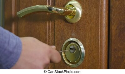 Locking up or unlocking door with key in hand.