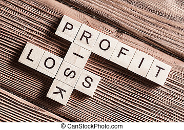 Profit loss and risk words on workplace collected of wooden cubes