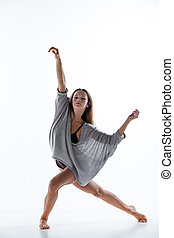 Young beautiful dancer in beige dress dancing on white...