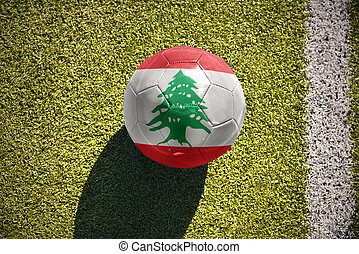 football ball with the national flag of lebanon lies on the...