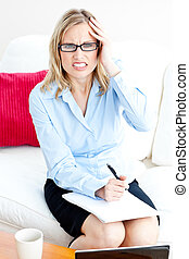 Tired businesswoman writing on her notepad having a headache at home in the living-room