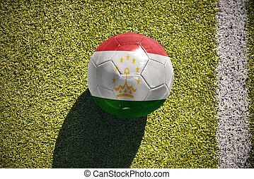 football ball with the national flag of tajikistan lies on...