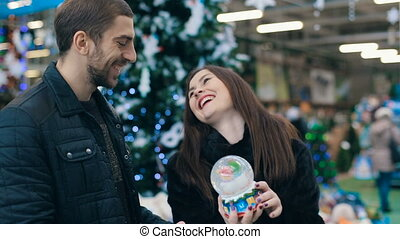 Couple with snow globe at store - Smiling couple chooses...
