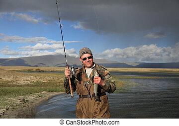 Fisherman with spinning catching fish in mountain lake Dayan...