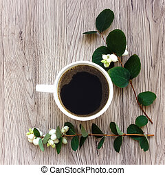 Cup of coffee decorated with green branches of ghostberry on...