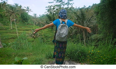 Russian female traveler dressed in casual blue clothing is standing in the middle of Indonesian endless fields, rising her hands and enjoying luxuriant tropical vegetation and fresh air around.