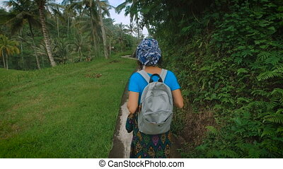 Young woman with a backpack walking along the stone footpath...