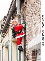 Santa hanging on the drainpipe - along the drainpipe next to...