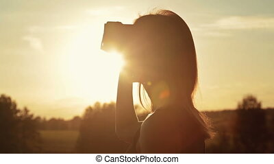 Woman uses a virtual reality glasses in the forest at sunset...