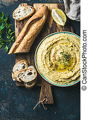 Homemade hummus with lemon, herbs and baguette over plywood...